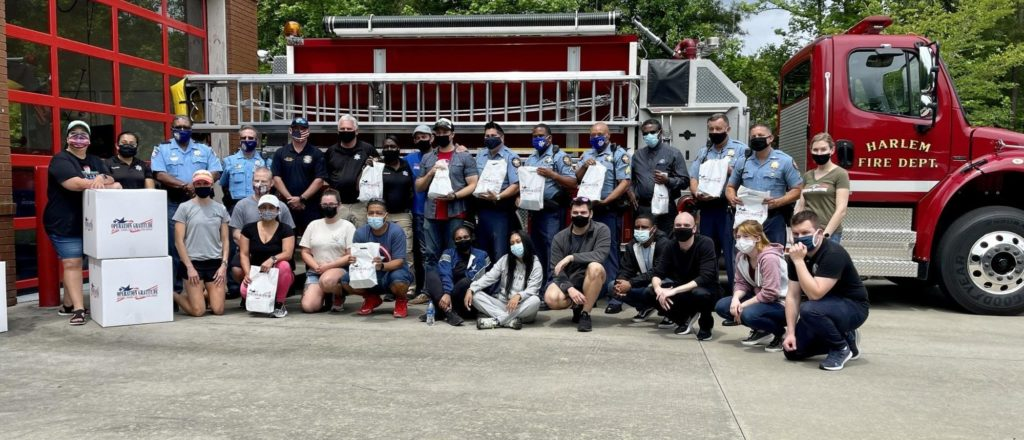First responder heroes stand in front of a fire truck with Operation Gratitude care packages.